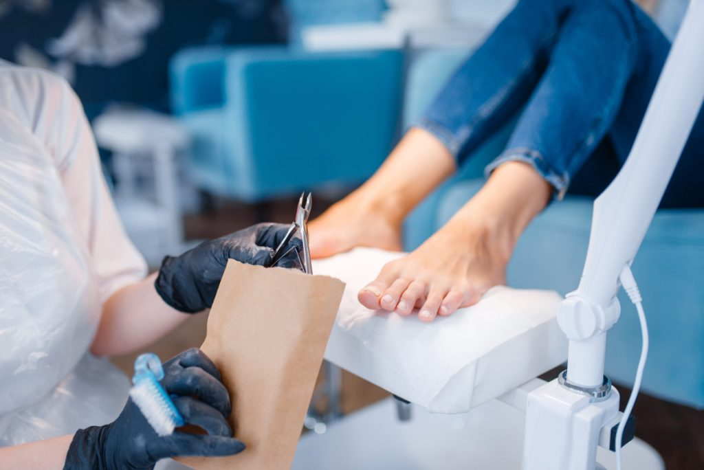 Cosmetologist salon, pedicure, clipping procedure. Nail care treatment for female client in beauty shop, doctor in gloves works with customer toenails