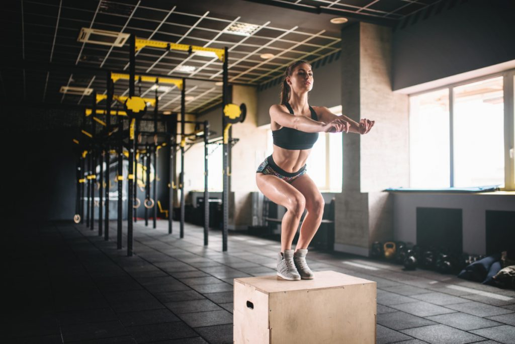 Woman Doing Box Jump Exercise In Fitness Club